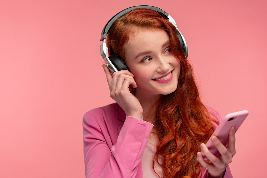 Beautiful young woman with headphones listening music on smart phone.