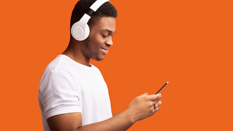 Smiling guy while listening to music on cellphone using headphone set.