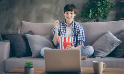A boy on the couch watching movie on a laptop.