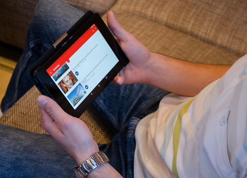 Person holding a tablet showing video on screen.