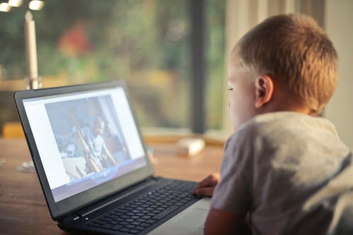 A boy watching video on a laptop